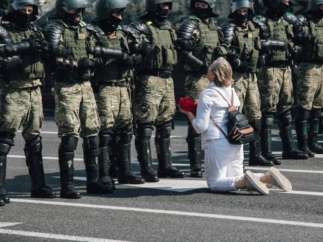 Eine Frau kniet vor einer Reihe Soldaten.