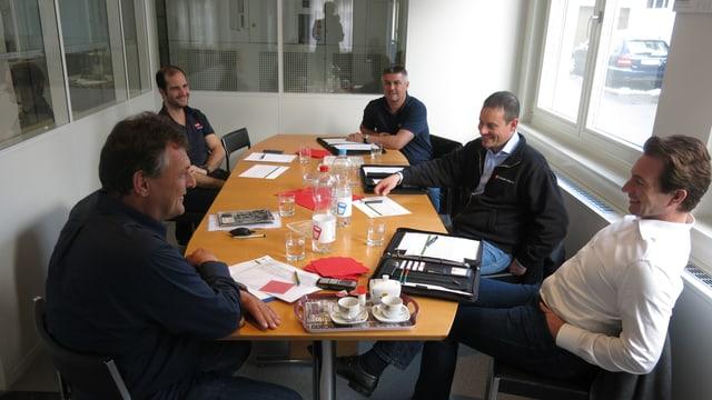 Die Leitung der vier Betriebe sitzen an einem Tisch und diskutieren.