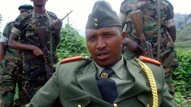 Ntaganda sitzt in Uniform mit Goldkordel und Käppi vor seinen bewaffneten Soldaten.
