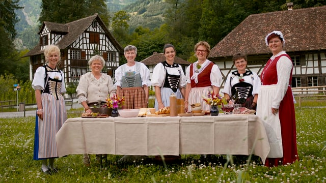 Sieben Landfrauen in ihren typischen Trachten.