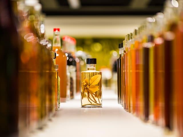 Eine Flaschenflucht, dazwischen ein kleines Glas, in dem eine gelbe Pfalnze eingelegt ist.