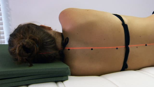 Frau liegt mit dem Rücken zum Betrachter. Punkte auf ihrer Wirbelsäule bilden eine gerade Linie, illustriert von einem Laserstrahl.