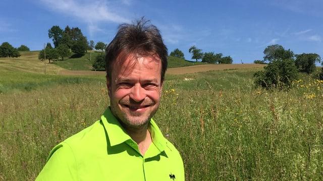 Mann in hellgrünem Hemd vor Wiese.