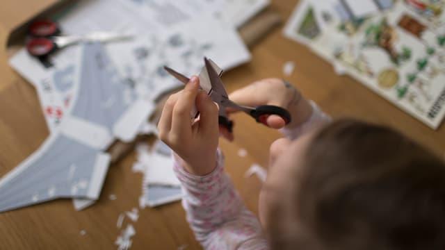 Kind schneidet Papier mit einer Schere.