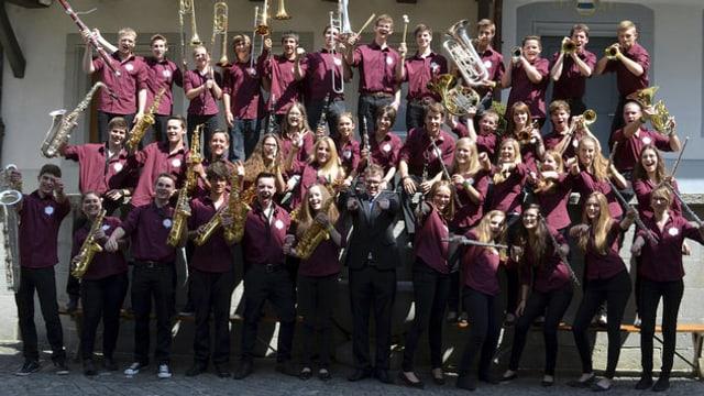 Die Musiker und Musikerinnen mit ihren Instrumenten zeigen sich auf dem Gruppenfoto ausgelassen.