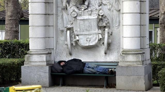 Mann ohne zu Hause schläft auf einer Bank.