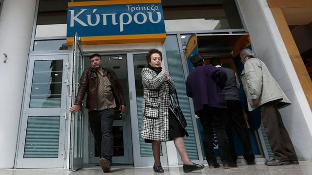 Menschen beim Eingang einer Bank.
