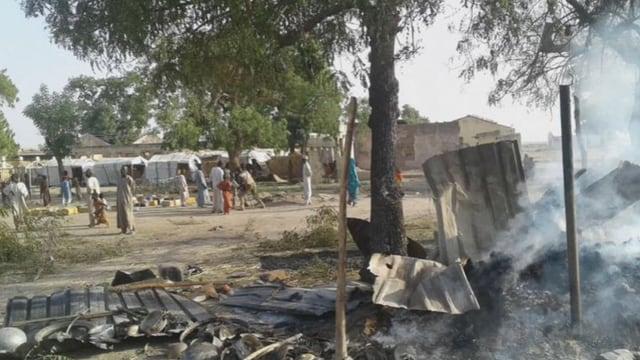 Zerstörte Teile eines Flüchtlingslagers und Menschen im Hintergrund.