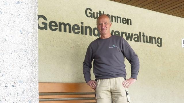 Mann steht an einer Hausmauer vor einer Sitzbank.