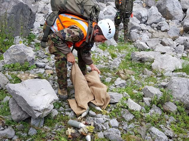 der junge Mann bückt sich zum Jutesack und am Boden liegen leere Munitionen