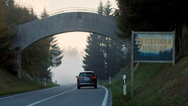 """Ein Auto auf einer Strasse. Daneben ein Ortsschild: """"Thallingen/Thallingue"""""""