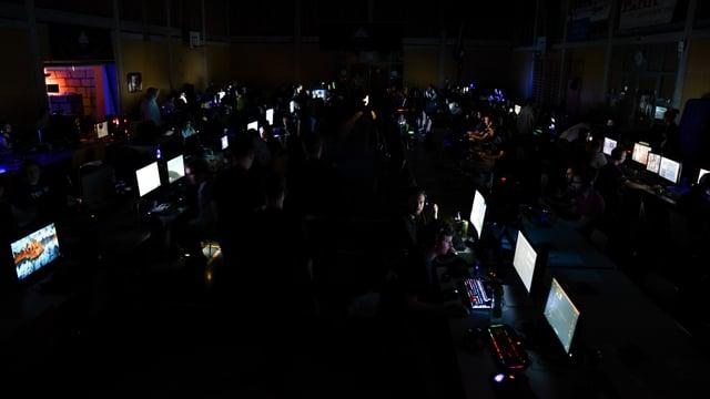 Dunkler Saal mit leuchtenden Computerbildschirmen