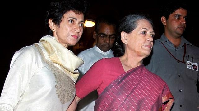 Sonia Gandhi wird von einer Kollegin gestützt.