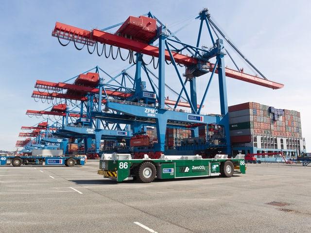 Ein AGV («Automated Guided Vehicle») rollt fahrerlos über den Platz der Hamburger Hafenanlage.