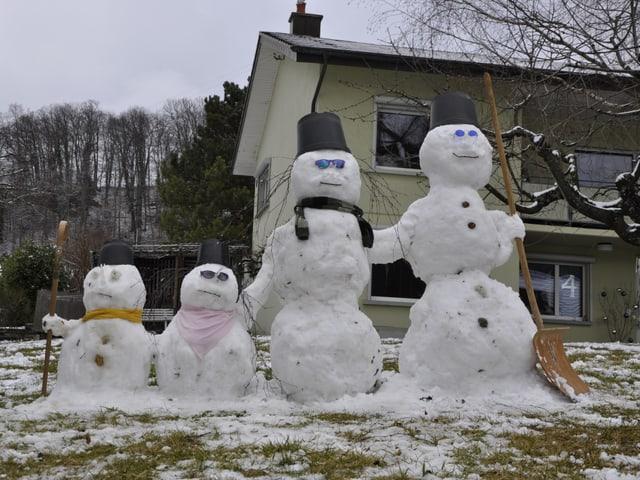 Eine Schneemann-Familie mit vier Schneemännern steht im praktisch schneefreien Garten vor einem Haus.