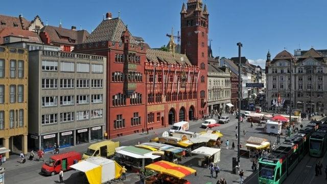 Sicht von oben auf Basler Markplatz mit dem Rathaus. Auf der Strasse fahren Auto und Velos, sowie das Tram.