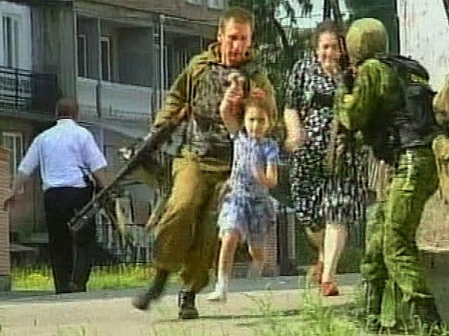 Bewaffnete Soldaten führen ein Mädchen und eine Frau von einer Schule weg.