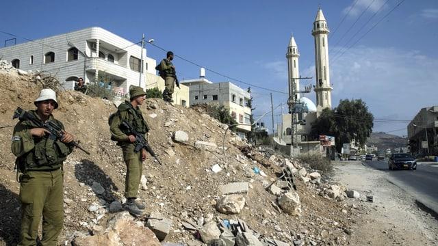 Bewaffnete Soldaten vor einem Haus, im Hintergrund die Minarette einer Moschee.