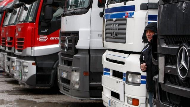 Eine Reihe Lastwagen, ein Mann mit Kapuze schaut zwischen zweien hervor.