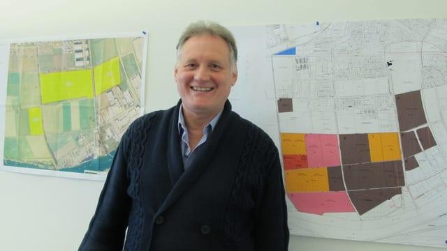 Ein Mann vor farbigen Plänen an der Wand.