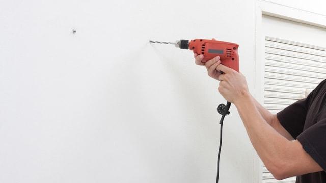 Mann bohrt ein Loch in eine Wand