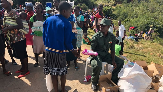 Ein Militärangehöroger verteilt Hilfsgüter