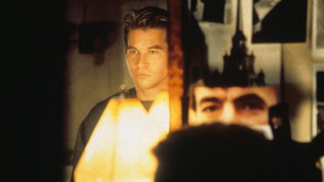 Ein Mann steht hinter einer Lampe.