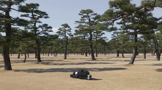 Filmszene: Ein Mann liegt zusammengekauert am Boden zwischen Bäumen