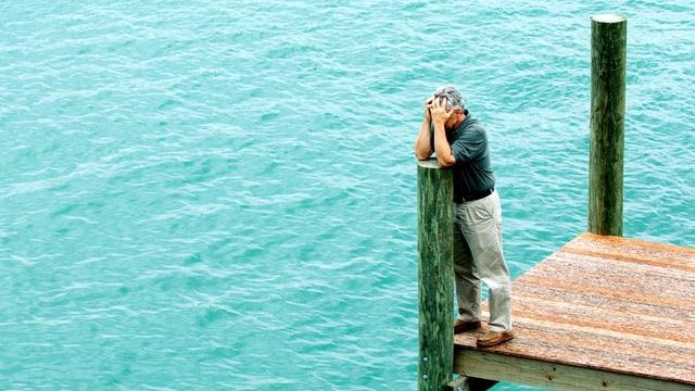 Ein Mann steht auf einem Steg, die Ellenbogen auf einen Pfeiler gestützt, das Gesicht in den Händen.
