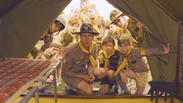 Edward Norton als Pfadfinderleiter und eine Gruppe Pfadfinder schauen überrascht ins Innere eines offenes Zelt.