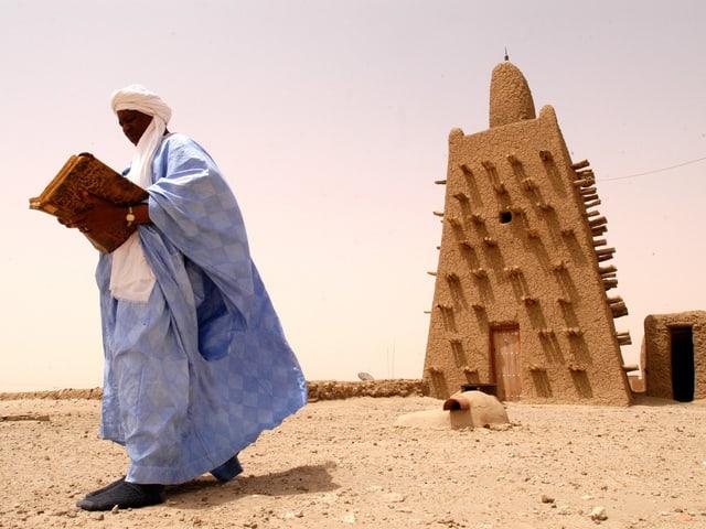 Mann mit Umhang und Turban liest in einem alten Buch auf dem Dach eines steinern Gebäudes.