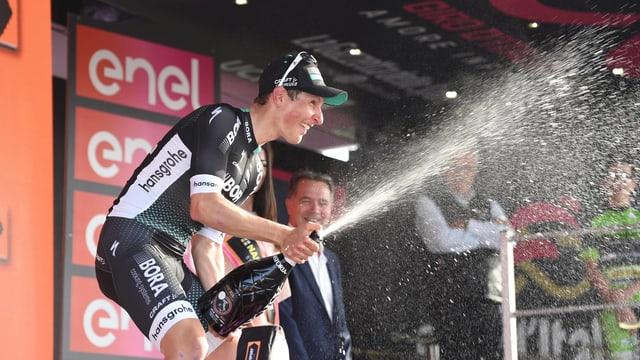 Lukas Pöstlberger schüttelt eine Champagnerflasche.