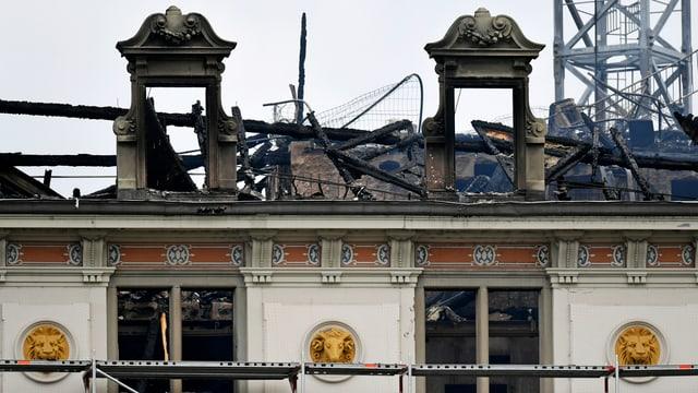 Alte geschmückte Hausfassade vor ausgebranntenm Dachstock
