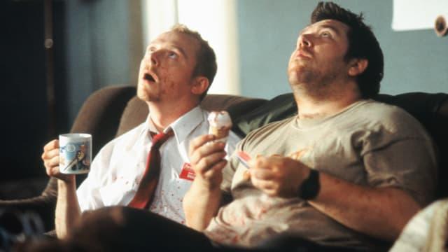 zwei Männer - blutbefleckt - sitzen auf der Couch, schauen zur Decke und trinken Tee.