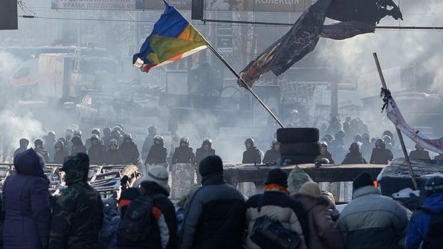 Demonstranten auf einer Strasse mit einer Ukrainen-Fahne.