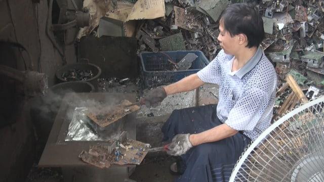 Chinesischer Arbeiter sitz umhüllt vor rauchender Computerplatte