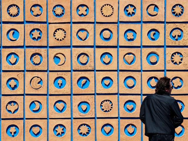 Ein Mann steht vor einer Wand mit Tonkacheln.