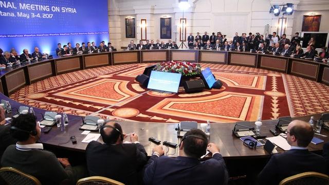 Die Teilnehmer sitzen an einem grossen runden Konferenztisch.