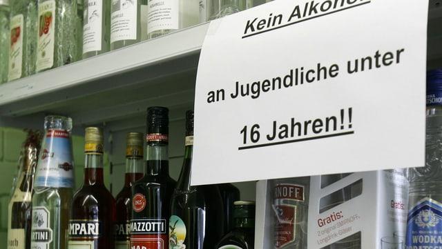 Regal mit Alkoholflaschen und einem Hinweis, dass kein Alkohol an Jugendliche verkauft werden darf.