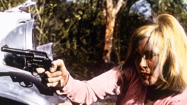 Bild eines eingefärbten schwarzweiss Filmes mit einer Frau die mit einem Revolver auf etwas zielt.