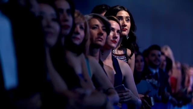 Symbolbild: Eine Reihe Personen wartet auf den Wahlkampfauftritt von Hillary Clinton.