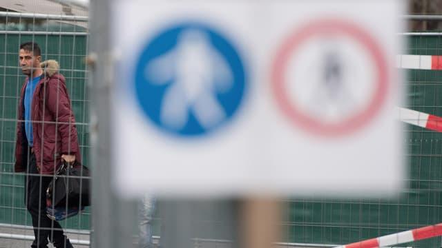 Ein Mann mit dunkelroter Jacke und einer Tasche hinter einer Abschrankung, davor ein Verkehrsschild.