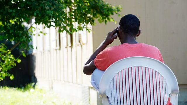Blick auf einen telefonierenden Asylbewerber von hinten.