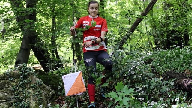 Sofie Bachmann im Dress der Nationalmannschaft rennt durch den Wald. Neben ihr ein OL-Posten bestehend aus einer kleinen Flagge.
