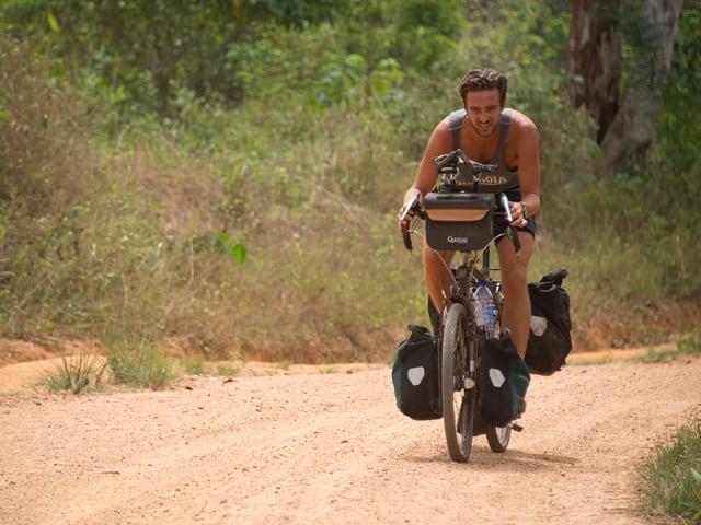 Lukas Biry unterwegs, Taschen links und rechts der beiden Räder sind voll beladen.