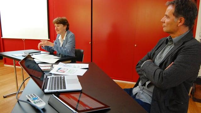 Mann und Frau am Tisch mit Laptops.