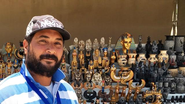 Ein Mann mit Mütze vor einem Stand mit ägyptischen Souvenirs.