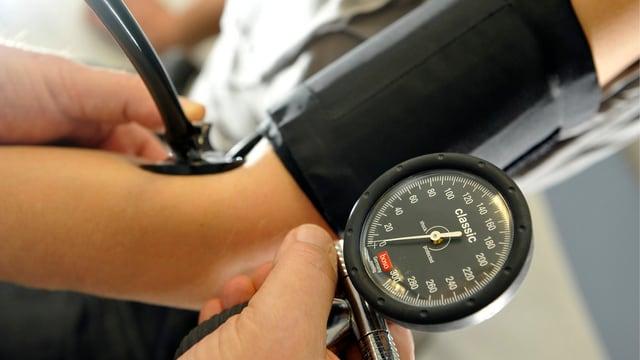 Ein Arzt misst den Blutdruck.