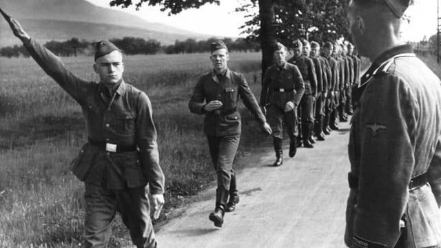 Junge Männer marschieren in Uniform auf einer Landstrasse, einer zeigt den Hitlergruss.