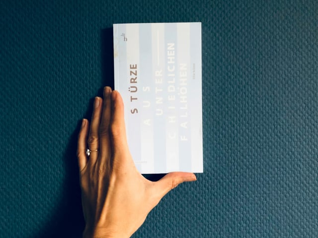 Der Erzählband «Stürze aus unterschiedlichen Fallhöhen» von Elise Schmit vor einer blauen Tapetenwand